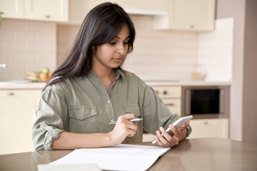 Young woman on mobile phone writing in a notebook
